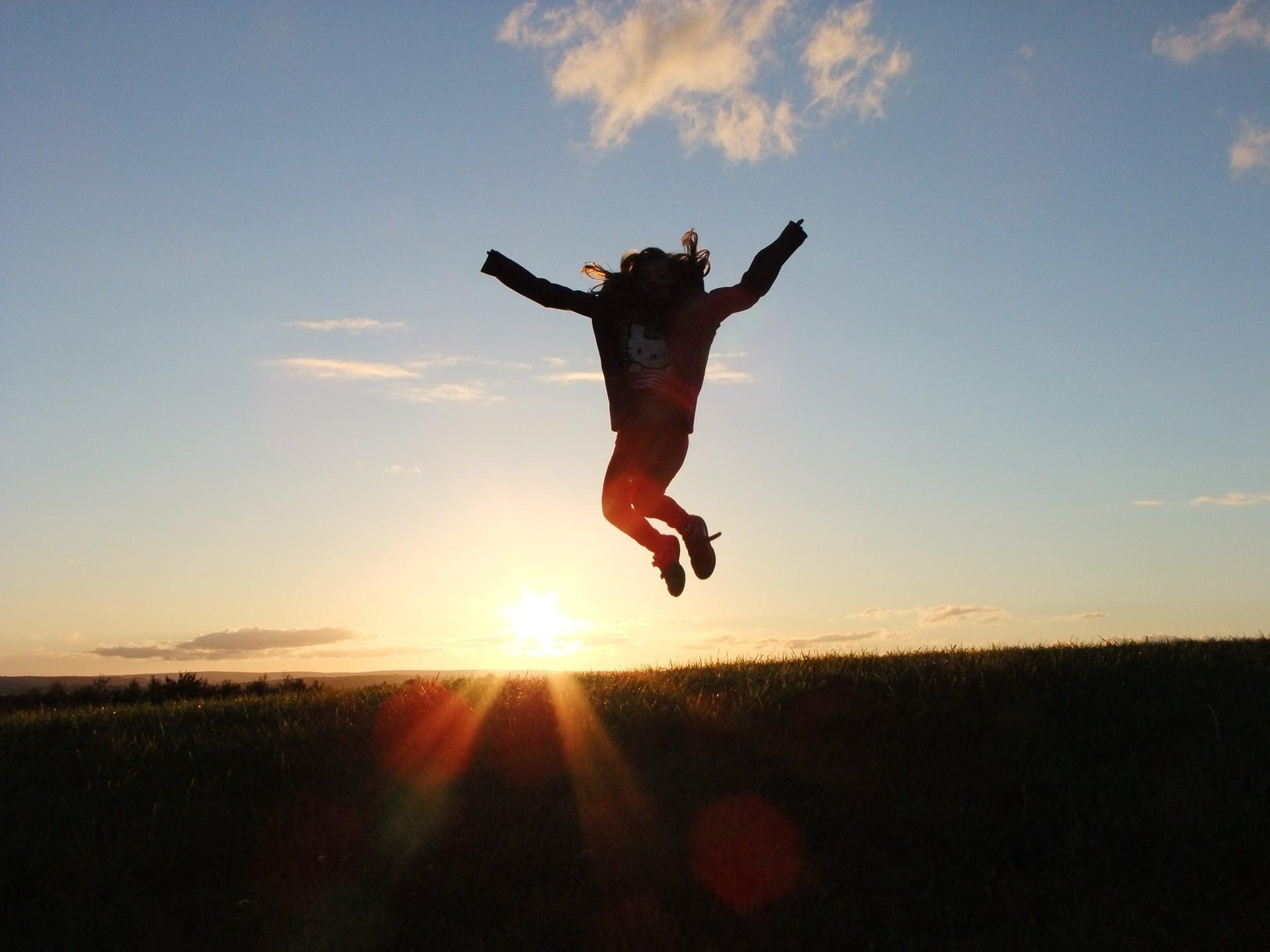 Photo d'un enfant qui saute en l'air devant un coucher de soleil pour représenter le succès vers lequel le coach vous amène.
